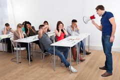 Teacher shouting through megaphone on university students. Angry teacher shouting through megaphone on university students in classroom Stock Photos