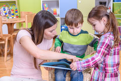 Teacher Showing a Book to Boy and Girl at the Nurcery. Teacher with Children at the Nurcery Royalty Free Stock Images