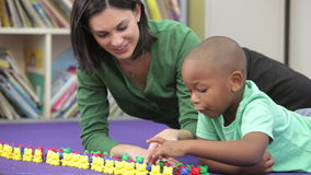 Teacher Showing Boy How To Count With Plastic Toys stock video footage