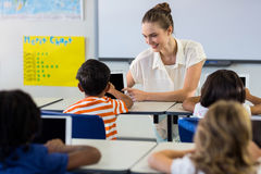 Teacher showing digital tablet to boy. Happy teacher showing digital tablet to boy in classroom Royalty Free Stock Image