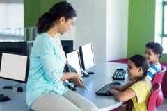 Teacher showing digital tablet to children. Female teacher showing digital tablet to children in computer class Stock Photos