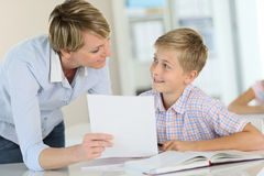Teacher showing excercise to pupil. Teacher showing paper to pupil in class Stock Photos