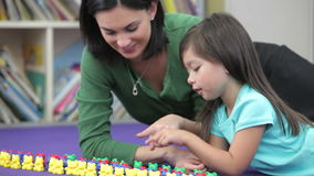 Teacher Showing Girl How To Count With Plastic Toys stock video footage