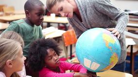 Teacher showing a globe to her pupils stock video footage