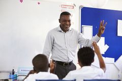 Teacher showing hand in front of an elementary school class Royalty Free Stock Images