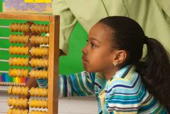 A teacher showing how to use a abacus. A student using an abacus to do a math problem stock photography