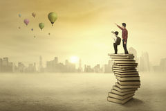 Teacher showing an inspiration to his student. Teacher and his student standing on a pile of books looking at air balloon on the sky Royalty Free Stock Photography