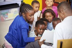 Teacher showing kids a book during elementary school lesson stock image