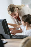 Teacher showing little girl how to use computer Royalty Free Stock Photography