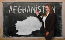 Teacher showing map of afghanistan on blackboard. Successful, beautiful and confident young woman showing map of afghanistan on blackboard for presentation Royalty Free Stock Images