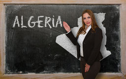 Teacher showing map of algeria on blackboard Stock Photos