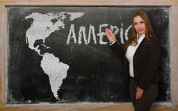 Teacher showing map of america on blackboard. Successful, beautiful and confident young woman showing map of america on blackboard for presentation, marketing Royalty Free Stock Images