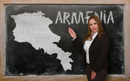 Teacher showing map of armenia on blackboard. Successful, beautiful and confident young woman showing map of armenia on blackboard for presentation, marketing Stock Photography