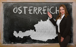 Teacher showing map of austria on blackboard. Successful, beautiful and confident young woman showing map of austria on blackboard for presentation, marketing Stock Photography