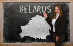 Teacher showing map of belarus on blackboard. Successful, beautiful and confident young woman showing map of belarus on blackboard for presentation, marketing Royalty Free Stock Image