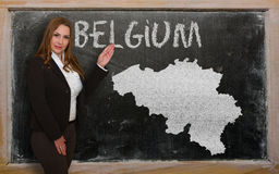 Teacher showing map of belgium on blackboard. Successful, beautiful and confident young woman showing map of belgium on blackboard for presentation, marketing Stock Photo