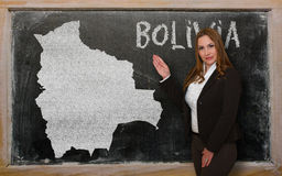 Teacher showing map of bolivia on blackboard. Successful, beautiful and confident young woman showing map of bolivia on blackboard for presentation, marketing Stock Photos