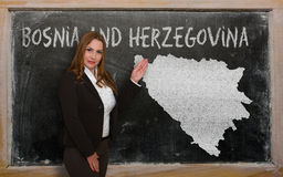 Teacher showing map of bosnia herzegovina. Successful, beautiful and confident young woman showing map of bosnia herzegovina on blackboard for presentation Stock Images