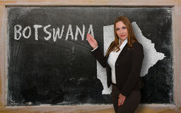 Teacher showing map of botswana on blackboard. Successful, beautiful and confident young woman showing map of botswana on blackboard for presentation, marketing Royalty Free Stock Images