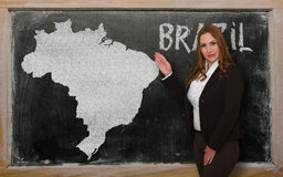 Teacher showing map of brazil on blackboard. Successful, beautiful and confident young woman showing map of brazil on blackboard for presentation, marketing Stock Photography
