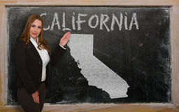 Teacher showing map of california on blackboard. Successful, beautiful and confident young woman showing map of california on blackboard for presentation Royalty Free Stock Photography