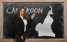 Teacher showing map of cameroon on blackboard. Successful, beautiful and confident young woman showing map of cameroon on blackboard for presentation, marketing Royalty Free Stock Photo