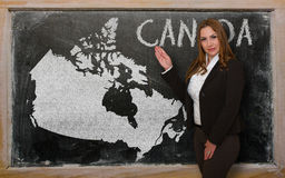 Teacher showing map of canada on blackboard. Successful, beautiful and confident young woman showing map of canada on blackboard for presentation, marketing Stock Photo