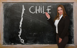 Teacher showing map of chile on blackboard. Successful, beautiful and confident young woman showing map of chile on blackboard for presentation, marketing Stock Image