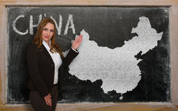 Teacher showing map of china on blackboard. Successful, beautiful and confident young woman showing map of china on blackboard for presentation, marketing Stock Photo