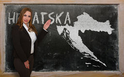 Teacher showing map of croatia on blackboard. Successful, beautiful and confident young woman showing map of croatia on blackboard for presentation, marketing Stock Photo