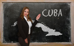 Teacher showing map of cuba on blackboard. Successful, beautiful and confident young woman showing map of cuba on blackboard for presentation, marketing research Stock Photography