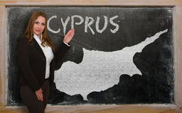 Teacher showing map of cyprus on blackboard. Successful, beautiful and confident young woman showing map of cyprus on blackboard for presentation, marketing Royalty Free Stock Photos