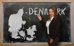 Teacher showing map of denmark on blackboard Stock Image