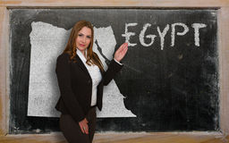 Teacher showing map of egypt on blackboard. Successful, beautiful and confident young woman showing map of egypt on blackboard for presentation, marketing Stock Image