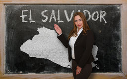 Teacher showing map of el salvador on blackboard. Successful, beautiful and confident young woman showing map of el salvador on blackboard for presentation Royalty Free Stock Photos