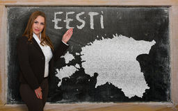 Teacher showing map of estonia on blackboard. Successful, beautiful and confident young woman showing map of estonia on blackboard for presentation, marketing Stock Photography