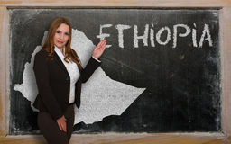 Teacher showing map of ethiopia on blackboard. Successful, beautiful and confident young woman showing map of ethiopia on blackboard for presentation, marketing Royalty Free Stock Photo