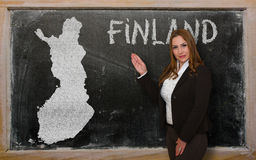 Teacher showing map of finland on blackboard. Successful, beautiful and confident young woman showing map of finland on blackboard for presentation, marketing Royalty Free Stock Photo