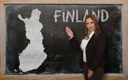 Teacher showing map of finland on blackboard Royalty Free Stock Photo