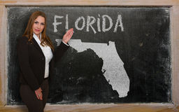 Teacher showing map of florida on blackboard. Successful, beautiful and confident young woman showing map of florida on blackboard for presentation, marketing Stock Photography