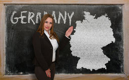 Teacher showing map of germany on blackboard. Successful, beautiful and confident young woman showing map of germany on blackboard for presentation, marketing Stock Photography