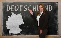 Teacher showing map of germany on blackboard. Successful, beautiful and confident young woman showing map of germany on blackboard for presentation, marketing Royalty Free Stock Images
