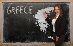 Teacher showing map of greece on blackboard. Successful, beautiful and confident young woman showing map of greece on blackboard for presentation, marketing Royalty Free Stock Image