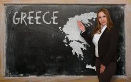 Teacher showing map of greece on blackboard Royalty Free Stock Image