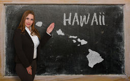 Teacher showing map of hawaii on blackboard. Successful, beautiful and confident young woman showing map of hawaii on blackboard for presentation, marketing Royalty Free Stock Photos