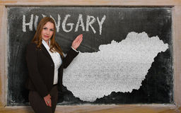 Teacher showing map of hungary on blackboard. Successful, beautiful and confident young woman showing map of hungary on blackboard for presentation, marketing Stock Photo