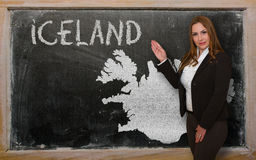 Teacher showing map of iceland on blackboard. Successful, beautiful and confident young woman showing map of iceland on blackboard for presentation, marketing Stock Photos