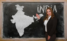 Teacher showing map of india on blackboard. Successful, beautiful and confident young woman showing map of india on blackboard for presentation, marketing Stock Photo