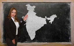 Teacher showing map of india on blackboard. Successful, beautiful and confident young woman showing map of india on blackboard for presentation, marketing Royalty Free Stock Image