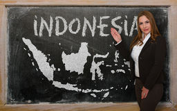 Teacher showing map of indonesia on blackboard Stock Photo